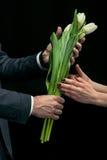 Укомплектуйте личным составом представлять тюльпаны к женщине на черной, международной концепции дня ` s женщин Стоковые Фото