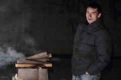 Укомплектуйте личным составом приготовление на гриле на ноче с огнем который слишком большой Стоковое фото RF