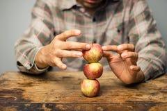Укомплектуйте личным составом пробовать сбалансировать яблока на верхнем одине другого Стоковые Изображения