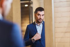 Укомплектуйте личным составом пробуя куртку дальше на зеркале в магазине одежды Стоковая Фотография