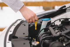 Укомплектуйте личным составом проверять уровень масла в его автомобиле используя dipstick Стоковые Фотографии RF