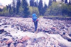 Укомплектуйте личным составом путешественника с большими крестами рюкзака река горы Стоковые Фотографии RF