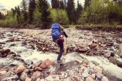Укомплектуйте личным составом путешественника с крестами рюкзака река горы Винтажное ima Стоковые Изображения