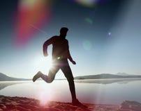 укомплектуйте личным составом работать и протягивать на пляже озера на восходе солнца Здоровый уклад жизни Одна молодая тренировк Стоковое Изображение RF