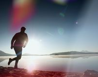 укомплектуйте личным составом работать и протягивать на пляже озера на восходе солнца Здоровый уклад жизни Одна молодая тренировк Стоковая Фотография RF