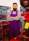 Укомплектуйте личным составом работника показывая его рабочее место в мастерской мотоцикла Стоковая Фотография RF