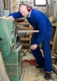 Укомплектуйте личным составом работу на машине на деревянной мастерской Стоковые Фотографии RF