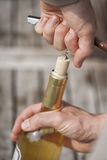 Укомплектуйте личным составом раскупоривать бутылку белого вина с штопором стоковые фотографии rf
