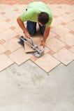 Укомплектуйте личным составом резать керамические плитки пола с ручным резцом Стоковая Фотография