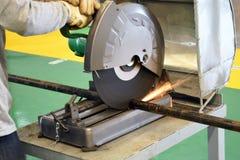 Укомплектуйте личным составом резать трубу с точильщиком на мастерской Стоковое фото RF