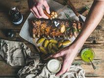 Укомплектуйте личным составом руки ` s держа вилку с стеклом картошки и пива Стоковое Фото