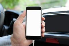 Укомплектуйте личным составом руку внутри автомобиля держа телефон с изолированным экраном стоковое изображение