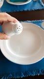 Укомплектуйте личным составом руку держа керамическое бутылки перца над белыми di Стоковые Фотографии RF