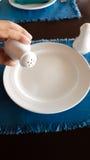 Укомплектуйте личным составом руку держа керамическое бутылки перца над белыми di Стоковое Изображение RF