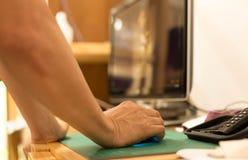Укомплектуйте личным составом руку держа мышь компьютера с экраном компьютера в задней части Стоковые Изображения