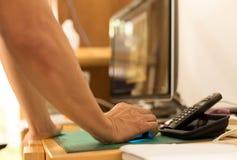 Укомплектуйте личным составом руку держа мышь компьютера с экраном компьютера в задней части Стоковое Фото