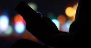Укомплектуйте личным составом руку используя ночу города ПК планшета в предпосылке сток-видео