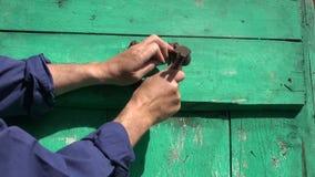 Укомплектуйте личным составом руку при молоток бить молотком ржавый horseshoe символ молотком везения на старой двери видеоматериал