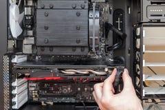 Укомплектуйте личным составом руку соединяя электропитание к видеокарте Стоковое фото RF