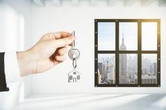 Укомплектуйте личным составом руку с ключом в комнате просторной квартиры пустой с видом на город Стоковые Фотографии RF