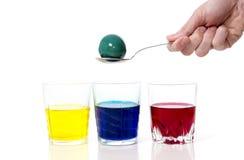 Укомплектуйте личным составом руку с ложкой, краской крася пасхальное яйцо Стоковое фото RF