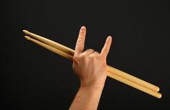 Укомплектуйте личным составом руку с drumsticks и рожками дьявола над чернотой Стоковое Изображение