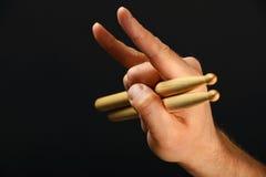 Укомплектуйте личным составом руку с drumsticks и рожками дьявола над чернотой Стоковое фото RF