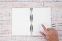 Укомплектуйте личным составом руку указывая тетрадь на деревянной таблице для текста и backgroun Стоковые Фотографии RF