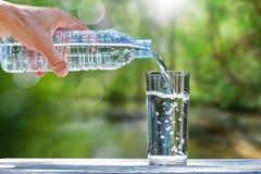 Укомплектуйте личным составом руку ` s держа воду бутылки питьевой воды и лить воду в стекло на деревянном столе на запачканной з Стоковые Фото