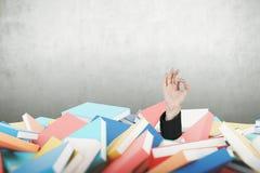Укомплектуйте личным составом руку s делая одобренный знак, кучу книг Стоковая Фотография
