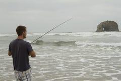 Укомплектуйте личным составом рыбную ловлю в прибое на пляже Rockaway стоковое изображение rf