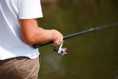 Укомплектуйте личным составом рыбную ловлю и владения двигая под углом штанга Стоковая Фотография RF