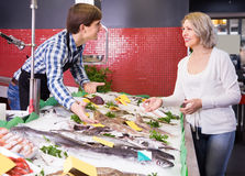 Укомплектуйте личным составом рыб продавца предлагая для того чтобы созреть клиент в магазине Стоковые Изображения