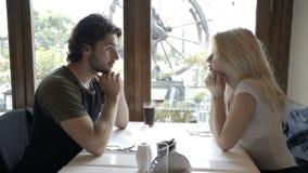 Укомплектуйте личным составом сидеть в пабе при его очаровательная подруга на таблице целуя ее руку сток-видео