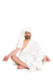 Укомплектуйте личным составом сидеть в положении лотоса, одетые одежды ванны стоковое изображение