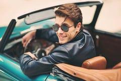 Укомплектуйте личным составом сидеть в роскошном ретро автомобиле cabriolet outdoors Стоковое Изображение RF