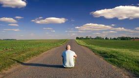 Укомплектуйте личным составом сидеть в середине проселочной дороги на солнечном лете Стоковая Фотография