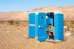 Укомплектуйте личным составом сидеть в туалете в середине пустыни - смерти Va Стоковое Фото