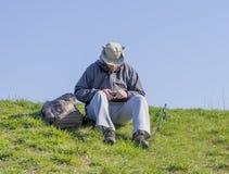 Укомплектуйте личным составом сидеть на линии травянистого вырезывания банка удя и подготавливать высокий Стоковые Фотографии RF