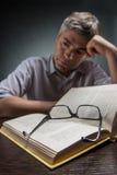 Укомплектуйте личным составом сидеть на коричневых таблице и книге чтения Стоковая Фотография