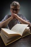 Укомплектуйте личным составом сидеть на коричневых таблице и книге чтения Стоковое фото RF