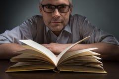 Укомплектуйте личным составом сидеть на коричневых таблице и книге чтения Стоковые Изображения