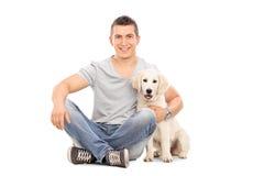 Укомплектуйте личным составом сидеть на поле и обнимать щенка Стоковое Изображение RF