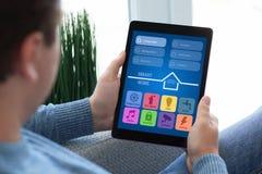 Укомплектуйте личным составом сидеть на софе держа дом app планшета умный стоковое фото rf