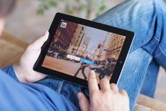 Укомплектуйте личным составом сидеть на софе и держать iPad с App LinkedIn на th стоковая фотография rf