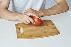 Укомплектуйте личным составом сидеть на таблице на белой предпосылке, томат, разделочная доска, овощи, диета, вегетарианство Стоковое Изображение
