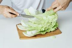 Укомплектуйте личным составом сидеть на таблице на белой предпосылке, салат, овощи, разделочная доска, диета, вегетарианство Стоковые Фотографии RF