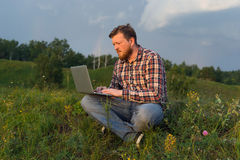 Укомплектуйте личным составом сидеть на траве с компьтер-книжкой на его коленях Стоковые Изображения