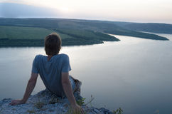 Укомплектуйте личным составом сидеть на утесе над рекой на заходе солнца Стоковое Изображение
