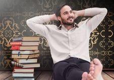 Укомплектуйте личным составом сидеть ослабленный при книги штабелированные античными обоями декоративными Стоковое Изображение